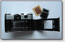 """Фото. 3. Полуразобранный фотоаппарат """"Зенит"""", текстолитовая плата и кусочек фотоплёнки."""